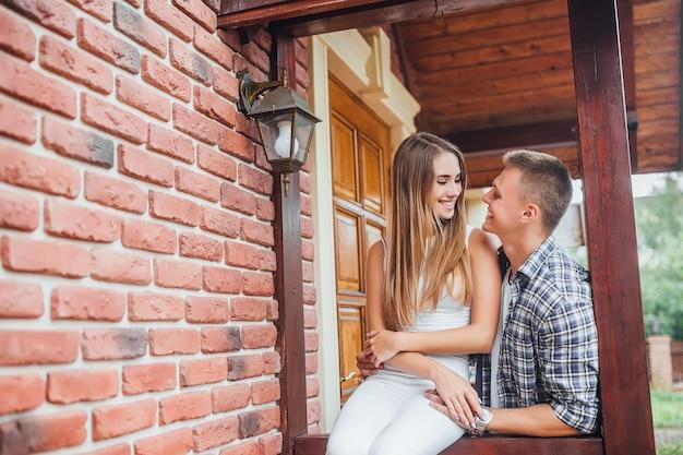 Giovane famiglia in piedi sotto il portico di casa