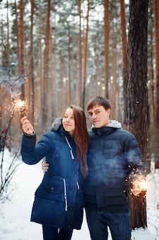 Giovane famiglia in piedi in una foresta di inverno con stelle filanti per l'umore festivo