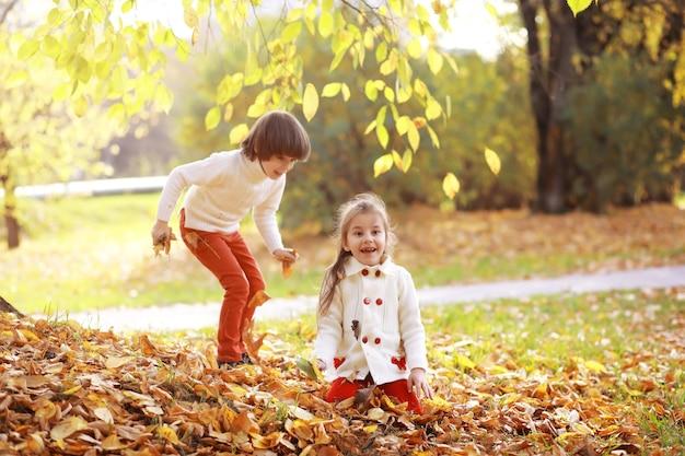 Giovane famiglia in una passeggiata nel parco autunnale in una giornata di sole. felicità di stare insieme.