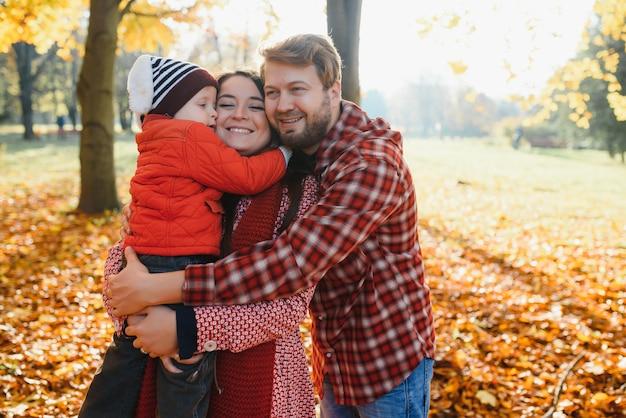 Giovane famiglia che cammina nel parco. autunno.