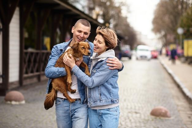 Giovane famiglia che cammina con un cane per le strade della città