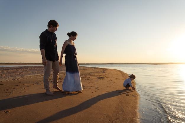 Una giovane famiglia con un figlio di 3 anni sta passeggiando lungo la selvaggia spiaggia serale. copia spazio.