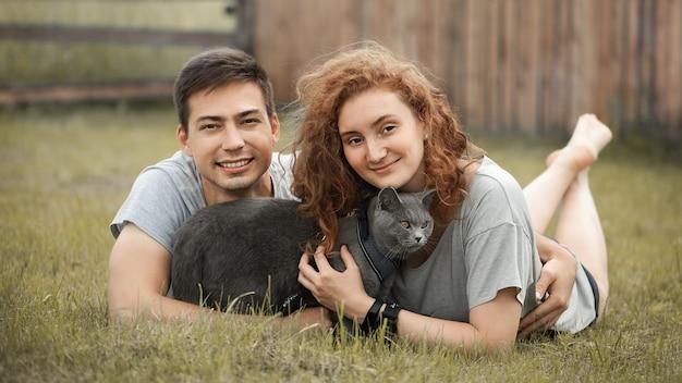 La giovane famiglia con un gatto sta riposando sull'erba