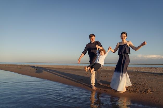 La giovane famiglia con il bambino si diverte sulla spiaggia. copia spazio.