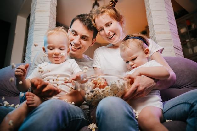 Giovane famiglia con bambini che mangiano popcorn sul divano di casa