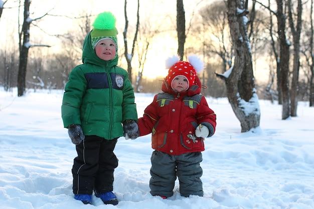 Giovane famiglia con bambini in una passeggiata nel parco in inverno