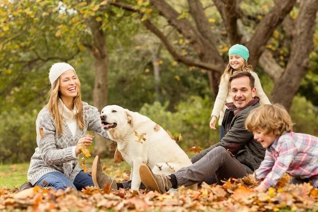 Giovane famiglia con un cane in foglie