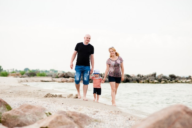 Giovane famiglia con suo figlio che cammina sul mare