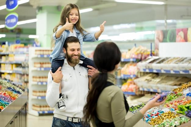 Una giovane famiglia con una bambina sceglie caramelle e cioccolato in un grande negozio, supermercato.