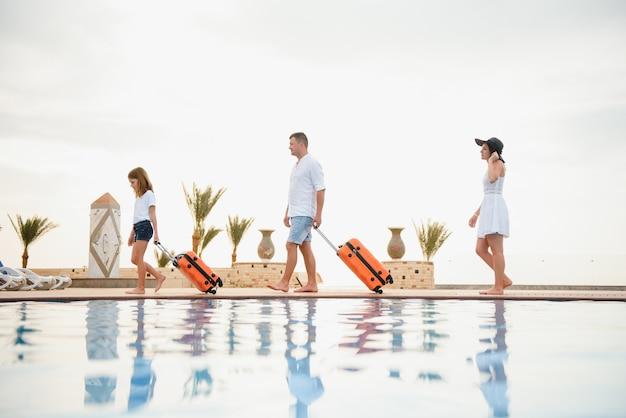 Giovane famiglia con le valigie che camminano all'edificio dell'hotel con una bellissima piscina.