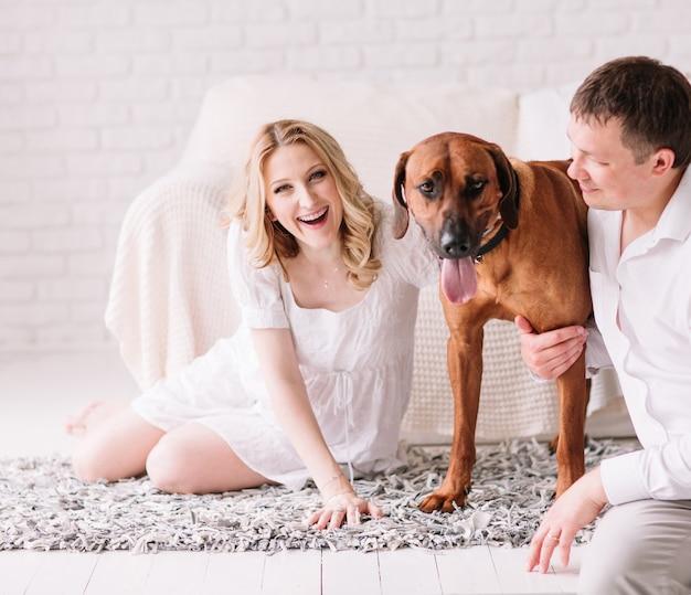 Giovane famiglia con il loro cane seduto sul letto in camera da letto. il concetto di una famiglia felice