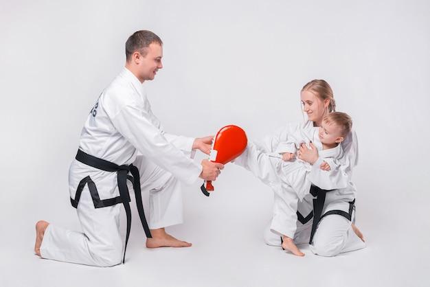 Giovane famiglia con il loro ragazzino a praticare arti marziali su bianco
