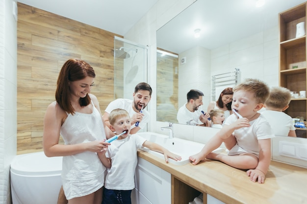 Giovane famiglia con due bambini piccoli che si divertono a lavarsi i denti insieme in bagno