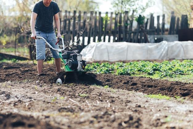 Il giovane giardiniere dell'agricoltore coltiva il rototiller del suolo