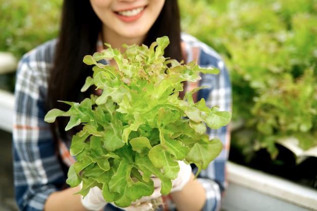 Giovane ragazza del coltivatore che tiene la lattuga della quercia rossa in azienda agricola idroponica con il sorriso