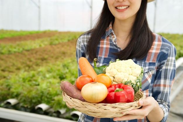 Giovane ragazza dell'agricoltore che tiene vario della merce nel carrello delle verdure con il sorriso