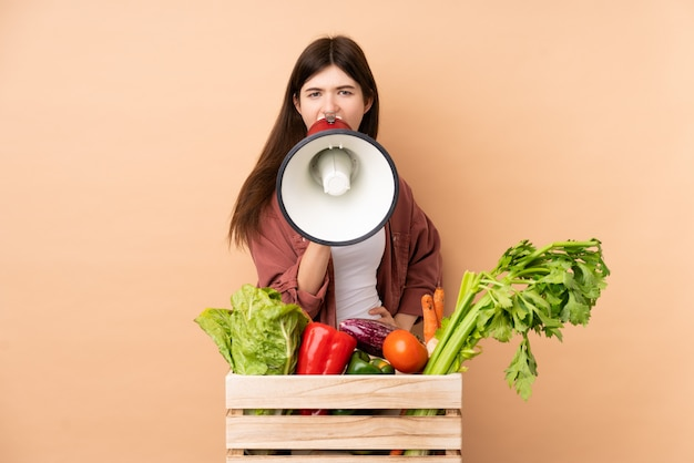 Ragazza giovane agricoltore con verdure appena raccolte in una scatola che grida tramite un megafono