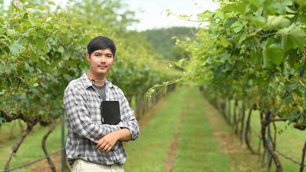 Un giovane agricoltore sta usando un tablet mentre si trova nel frutteto.