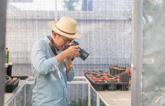 Uomo giovane agricoltore che cattura foto con la sua macchina fotografica nel giardino di cactus, concetti hobby