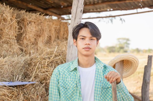 Uomo giovane agricoltore con forcone che guarda l'obbiettivo con balle sfocate di paglia pressata in stoccaggio di campagna rurale, concetto di agricoltore intelligente