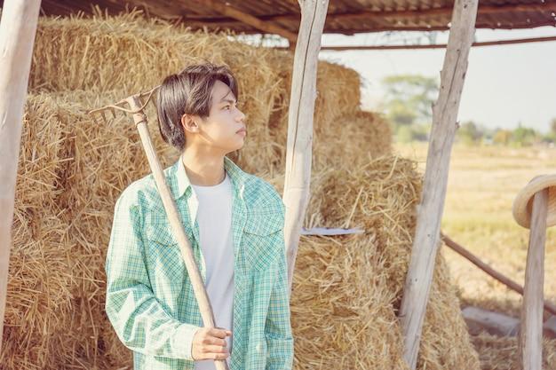 Uomo giovane agricoltore con forcone che guarda il cielo con balle sfocate di paglia pressata in stoccaggio di campagna rurale, concetto di contadino intelligente