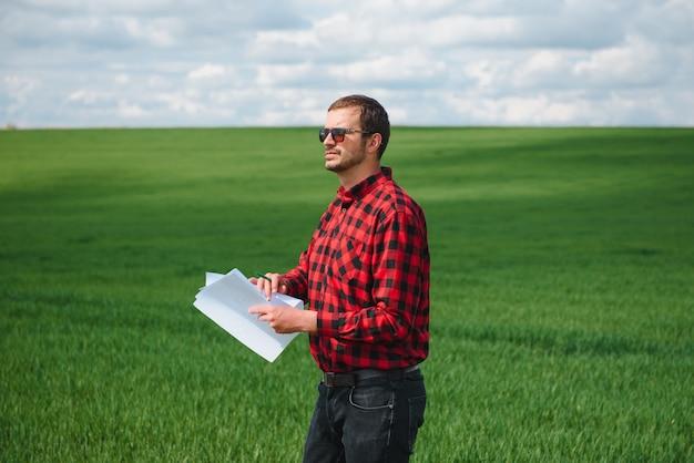 Giovane agricoltore su un campo di grano. frumento giovane in primavera. concetto di agricoltura. un agronomo esamina il processo di maturazione del grano nel campo. il concetto di azienda agricola