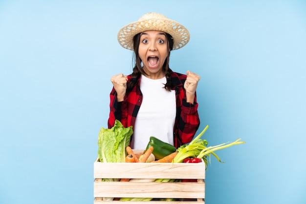 Giovane agricoltore donna che tiene la verdura fresca in un cesto di legno per celebrare una vittoria nella posizione del vincitore