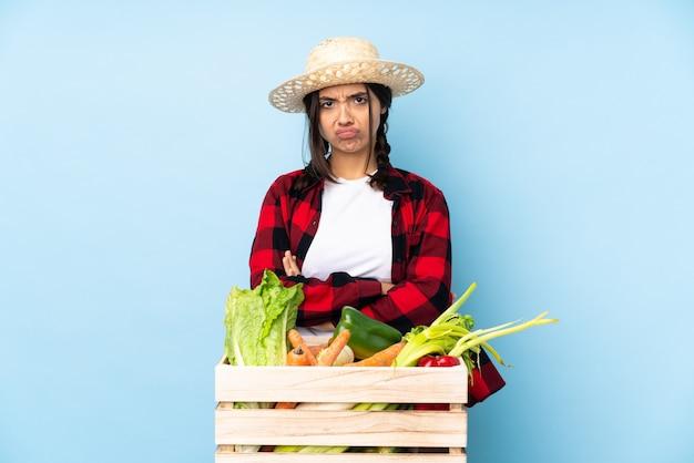 Giovane agricoltore donna che tiene le verdure fresche in un cestino di legno che si sente sconvolto