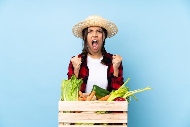 Giovane agricoltore donna che tiene la verdura fresca in un cesto di legno frustrata da una brutta situazione