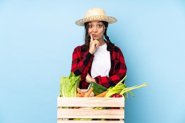 Giovane agricoltore donna che tiene la verdura fresca in un cesto di legno e guardando davanti