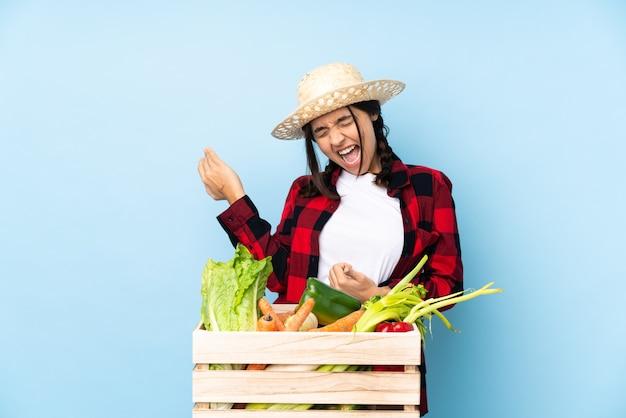 Giovane agricoltore donna che tiene la verdura fresca in un cestino di legno che fa il gesto della chitarra