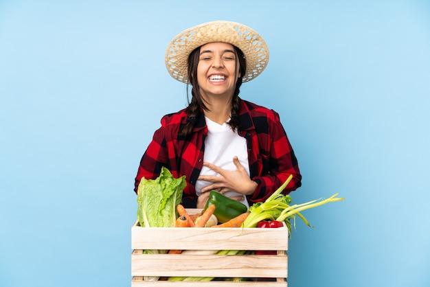Giovane agricoltore donna che tiene la verdura fresca in un cestino di legno che sorride molto