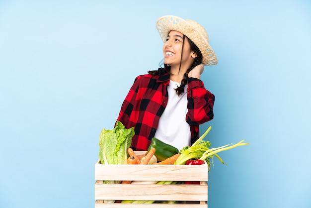 Giovane agricoltore donna che tiene la verdura fresca in un cesto di legno pensando un'idea