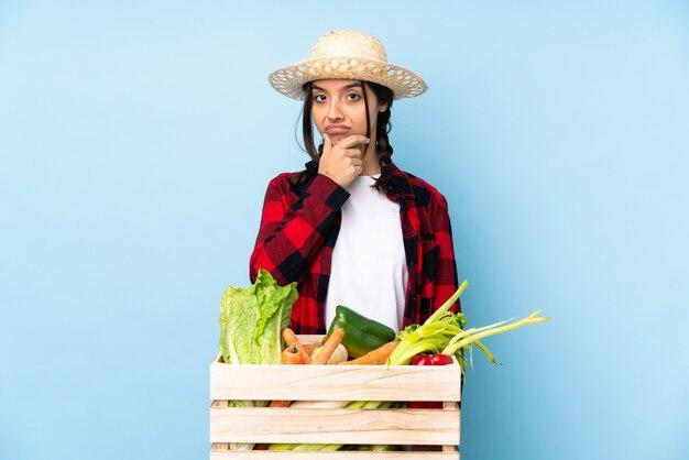 Giovane agricoltore donna che tiene le verdure fresche in un pensiero del cestino di legno