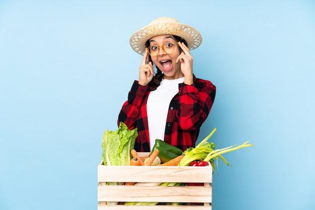 Giovane agricoltore donna che tiene le verdure fresche in un cestino di legno con gli occhiali e sorpreso
