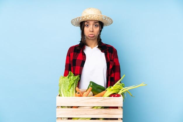Giovane agricoltore donna che tiene la verdura fresca in un cesto di legno con espressione triste e depressa