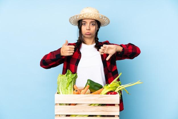 Giovane agricoltore donna che tiene la verdura fresca in un cesto di legno