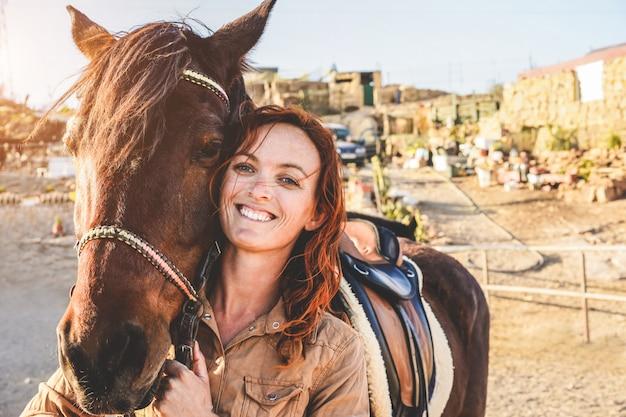 Donna giovane agricoltore che gioca con il suo cavallo in una giornata di sole all'interno del ranch di recinto - concetto di amore tra persone e animali - focus principale sull'occhio degli animali
