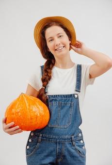 La giovane donna dell'agricoltore sorride con una zucca matura arancione su un fondo bianco concetto di giardinaggio