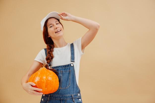 Una giovane contadina con un berretto bianco su sfondo giallo tiene in mano un grande raccolto autunnale di zucca