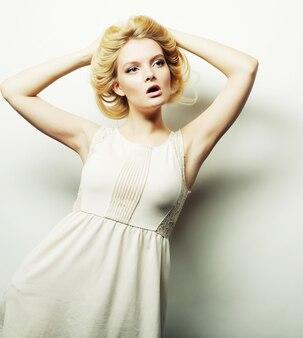 Moda giovane donna bionda in abito bianco in posa in studio