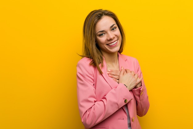 La giovane donna d'affari di moda ha un'espressione amichevole, premendo il palmo sul petto. concetto di amore.
