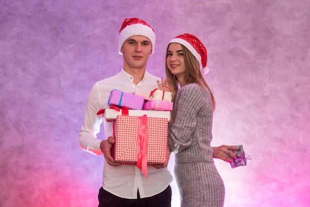 Giovane coppia alla moda che celebra il giorno di san valentino regalandosi regali l'un l'altro