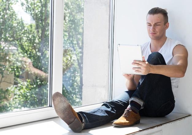 Moda giovane uomo seduto vicino alla finestra con tablet. concetto di stile di vita.