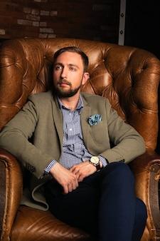 Giovane uomo di moda in giacca elegante seduto in poltrona di pelle in un moderno loft interno
