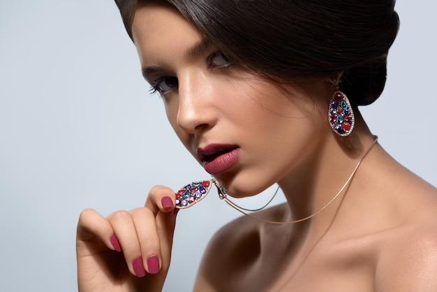 Giovane modella che guarda con ferocia e sicurezza indossando orecchini e una collana con pietre preziose multicolori