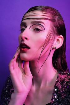 Modello di moda giovane in posa sulla porpora
