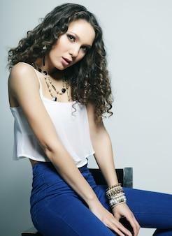 Giovane modella seduta su una sedia, ripresa in studio