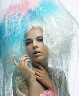 Giovane modella con trucco luminoso e capelli colorati