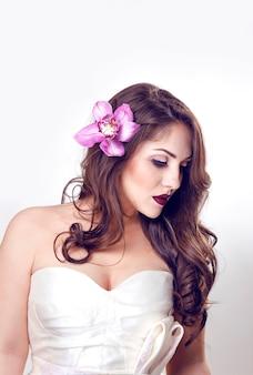 Giovane modella con gli occhi chiusi e il trucco, in abito da sposa con capelli mossi e fiore su di esso